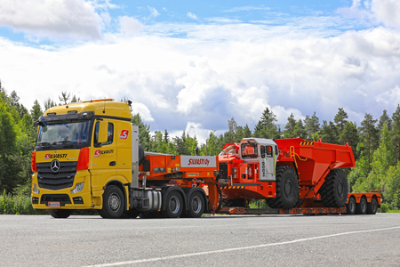 daimler: LEMPAALA, FINLAND - JULY 6, 2017: Transport of Sandvik TH550 Underground Truck by Silvasti Heavy Mercedes-Benz Actros 3351 on the asphalt yard of a truck stop. The TH550 has an operating weight of 35900 kg.