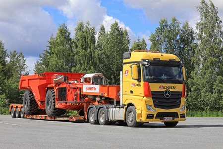 daimler: LEMPAALA, FINLAND - JULY 6, 2017: Transport of Sandvik TH550 Underground Truck by Silvasti Heavy Mercedes-Benz Actros 3351 on the asphalt yard of a truck stop at summer. The TH550 has an operating weight of 35900 kg.