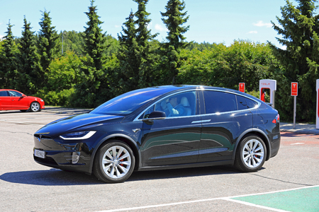 PAIMIO, FINLAND - JULY 14, 2017: Tesla Model X electric vehicle leaves Tesla Supercharger station. The Model X is an electric luxury crossover SUV manufactured by Tesla, Inc.