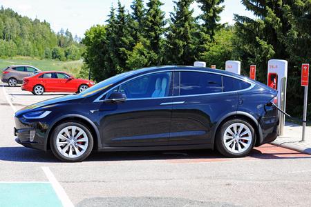 PAIMIO, FINNLAND - 14. JULI 2017: Das neue Elektroauto Tesla-Modells X wird bei Tesla Supercharger aufgeladen. Das Modell X ist ein Elektro-Luxus-Crossover-SUV, hergestellt von Tesla, Inc.