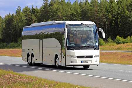 SALO, FINLAND - JULY 22, 2017: White Volvo coach bus moves along interstate among beautiful scenery at summer. Zdjęcie Seryjne - 83202255