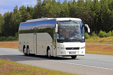 SALO, FINLANDIA - 22 DE JULIO DE 2017: El autobús blanco del autobús de Volvo se mueve a lo largo de la interestatal entre el paisaje hermoso en el verano. Editorial