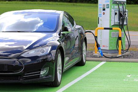 SALO, FINLAND - JUNE 25, 2017: Black Tesla Model S electric car charges battery.