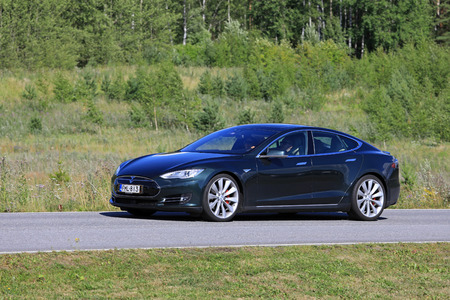 PAIMIO, FINLAND - JULY 29, 2017: Metallic green Tesla Model S electric car moves along rural road at summer with green forest and shrub on the background. Stock Photo - 83269313