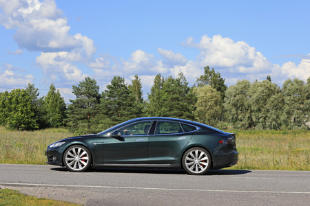 famous industries: PAIMIO, FINLAND - JULY 29, 2017: Metallic green Tesla Model S moves along rural road at summer with forest and beautiful sky on the background.