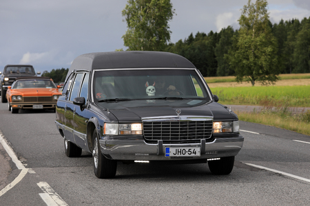 SOMERO, FINLAND - AUGUST 5, 2017: Tuned Cadillac Fleetwood funeral car with led lights and skull detail moves along scenic highway on Maisemaruise 2017 car cruise in Tawastia Proper, Finland. Public event.