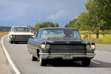 SOMERO, FINLAND - AUGUST 5, 2017: Classic black Cadillac moves along scenic highway with other vintage cars on Maisemaruise 2017 car cruise in Tawastia Proper, Finland. Public event.