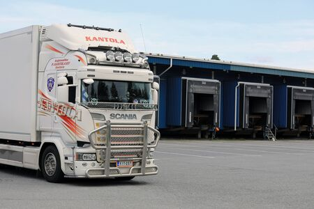 warehouse building: SEINAJOKI, FINLAND - AUGUST 12, 2017: Customized white Scania refrigerated transport truck of P Kantola Ky at the loading zone of a warehouse.