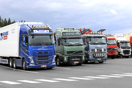 light duty: FORSSA, FINLAND - AUGUST 25, 2017: Colorful Volvo trucks parked on the asphalt yard of a truck stop on a cloudy day.
