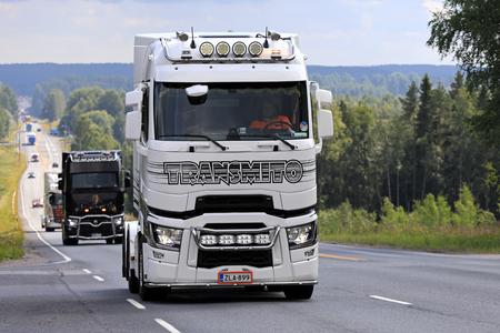 IKAALINEN, FINLANDIA - 10 DE AGOSTO DE 2017: El tractor semi modificado para requisitos particulares blanco y negro de Renault Trucks T con los accesorios ligeros de Transmito se mueve a lo largo del camino escénico en el convoy del camión para impulsar la demostración 2017, Finlandia del camión.