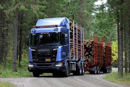 LAUKAA, FINLAND - SEPTEMBER 22, 2017: Scania R650 XT logging truck on a test drive along a small road in spruce forest during Scania Laukaa Tupaswilla Off-Road event.
