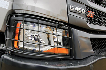 light duty: ORIPAA, FINLAND - SEPTEMBER 30, 2017: Detail of headlamp protection and grille of the new Scania XT G450 heavy duty truck in rain.