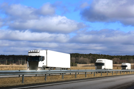 Three white semi trailer cargo trucks platoon on freeway at spring, with blue sky and clouds background. Copy space top of image.