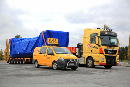 FORSSA, FINLAND - OCTOBER 13, 2017: Yellow MAN TGX 41.640 semi truck wide load transport and Mercedes-Benz pilot vehicle of Silvasti Heavy parked on the asphalt yard of a truck stop in South of Finland.