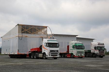 포자, 핀란드 -2011 년 8 월 10 일 : M. Kaleva 세미 트레일러 트럭에 의해 운반 조립식 된 집 모듈의 세 대형 특급 운송 운송, 흐린 아침에 트럭 정지 야드에  에디토리얼