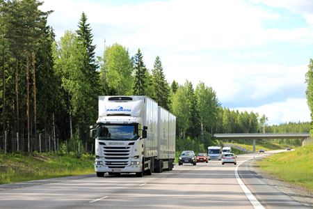 VAAJAKOSKI, FINLAND - JULY 7, 2017: White Scania combination vehicle of Finnish Kaukokiito for temperature controlled transport hauls goods among traffic at summer in Central Finland.