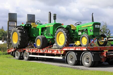 KOSKI TL, FINLAND - SEPTEMBER 1, 2017: Classic John Deere 510 and 5010 tractors, both manufactured in the 1960s, transported on vehicle trailer in South of Finland.