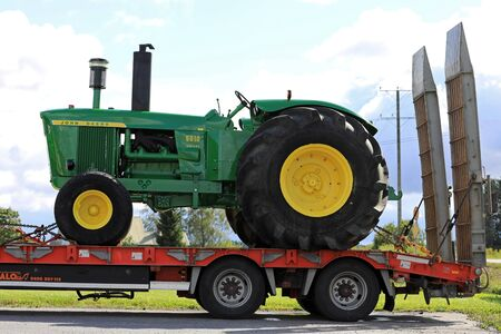 KOSKI TL, FINLAND - SEPTEMBER 1, 2017: Classic John Deere 5010 tractor transported on vehicle trailer in South of Finland. The 5010 was manufactured in 1963 - 1965.
