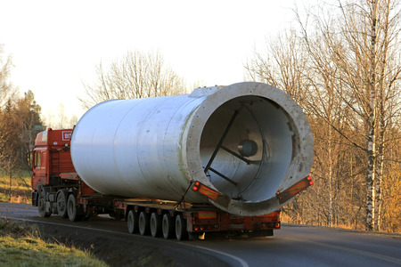 SOMERO, FINLAND - NOVEMBER 3, 2017: Oversize load semi trailer transport keeps left on the turn of a country lane during the transport of a wind turbine part in autumnal South of Finland at dusktime. Редакционное