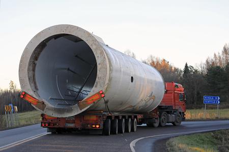SOMERO, FINLANDIA - 3 DE NOVIEMBRE DE 2017: El transporte del remolque de la carga de gran tamaño gira a la derecha en el cruce del país durante el transporte de la parte de una turbina de viento en el sur otoñal de Finlandia en el dusktime.