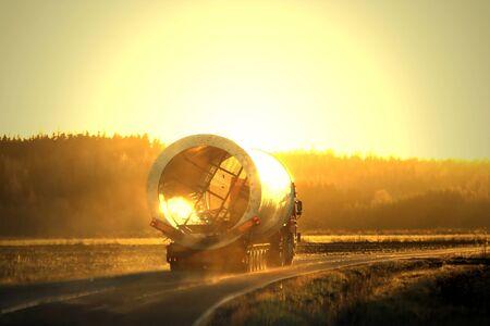 Oversize load semi trailer transport moves along rural road in autumnal fog at sunset.