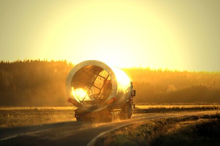 Oversize load semi trailer transport moves along rural road in autumnal fog at sunset.