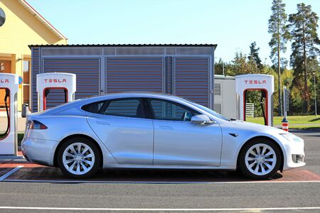 TOIJALA, FINLAND - SEPTEMBER 24, 2017: Silver Tesla Model S fully electric car charges battery at Tesla Supercharger charging station in Toijala, Finland.
