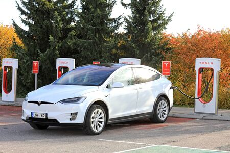 PAIMIO, FINLAND - OCTOBER 15, 2017: White Tesla Model X electric crossover SUV charges battery at Tesla Supercharger station in Paimio.
