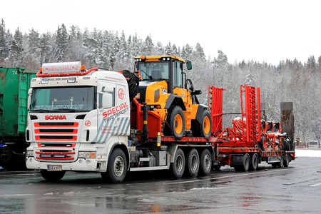 FORSSA, FINLAND - OCTOBER 27, 2017: Scania combination vehicle of S. Liikanen for Ahola Special Transport parked on a truck stop during the haul of a JCB wheel loader and Kuhn agricultural machinery in winter. Editorial