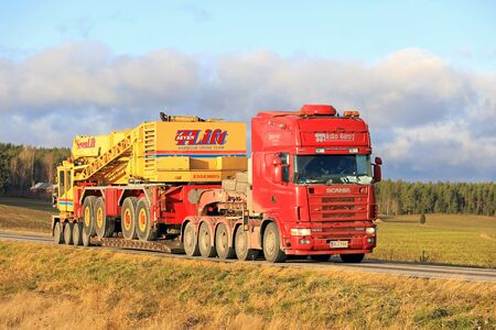 hauler: SALO, FINLAND - NOVEMBER 17, 2017: Red Scania 164G truck of Asko Haro Oy transports SevenLift harbour crane on drop deck trailer along highway in South of Finland.