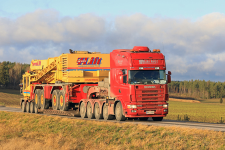 SALO, FINLAND - NOVEMBER 17, 2017: Red Scania 164G truck of Asko Haro Oy transports SevenLift harbour crane on drop deck trailer along highway in South of Finland.