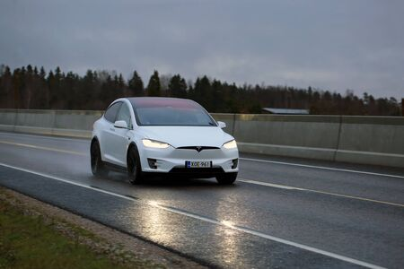 SALO, FINLAND - NOVEMBER 18, 2017: White Tesla Model X electric car moves along wet road in the evening. Editorial