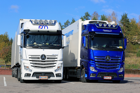 SALO, FINLANDIA - 8 DE OCTUBRE DE 2016: Los camiones blancos y azules del cargo de Mercedes-Benz Actros de FSN Logistics y Siirtolinja Oy para el transporte controlado de la temperatura estacionaron en yarda del asfalto en un día soleado de otoño.