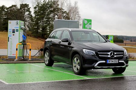SALO, FINLAND - NOVEMBER 18, 2017: New, black Mercedes-Benz GLE hybrid SUV charges battery on electric vehicle charging station in South of Finland.