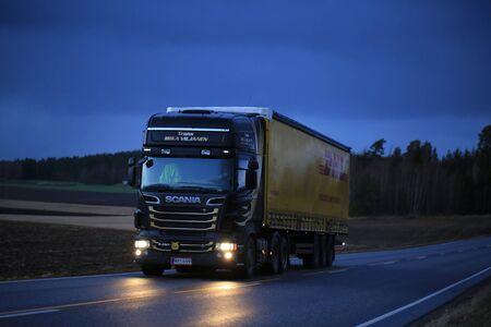 SALO, FINLAND - DECEMBER 8, 2017: Dark blue Scania R620 semi of Trans Mika Viljanen hauls DHL trailer along highway in the evening in South of Finland.