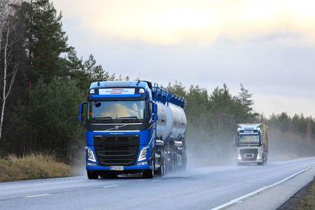 RAASEPORI, FINLAND - DECEMBER 27, 2017: Blue Volvo FH tank truck of Powder Trans and other Volvo truck transport goods along wet highway on a rainy day in winter.