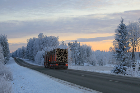 Landscape of a highway at winter dusk with frosted trees and logging truck that hauls a full timber load. Stock Photo - 95009701