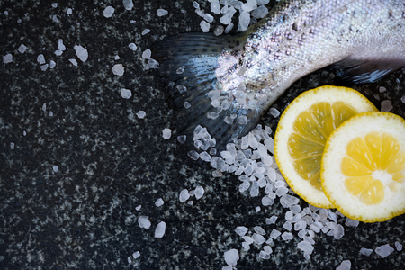 Delicious fresh raw fish on dark granite cutting board with lemon and salt. Vintage food background Stock Photo