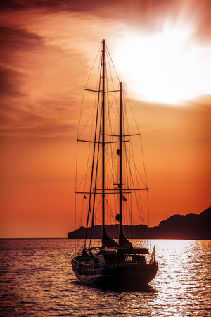 Old ship sailing to the sunset. Dramatic sea view