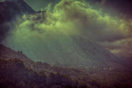dark city: Mystical mountains village landscape with fog. Vintage effect