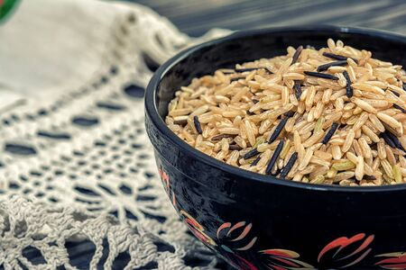 unpolished: Unpolished brown and black rice in wooden bowl on wooden background with rustic doily crochet Stock Photo