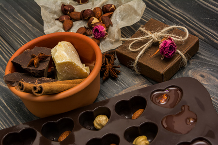 cioccolato natale: Homemade chocolate candys, cocoa, cocoa butter, nuts, present box, cinnamon and dry roses on wooden background