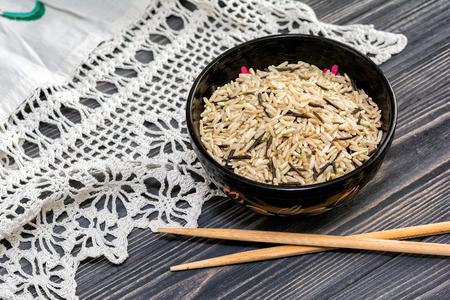 arroces: marr�n sin pulir y arroz negro en un taz�n de madera, palillos en el fondo de madera con Crochet tapete de r�stica. Comida sana