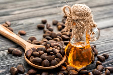 Cedar oil in bottle, cedar nuts, spoon on wooden background