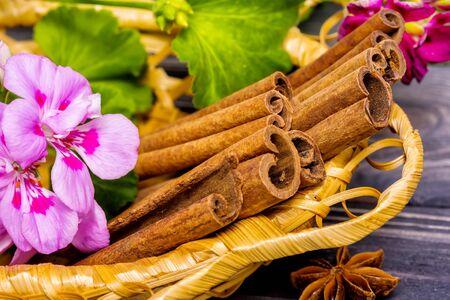 cinammon: Cinnamon sticks in straw basket with flowers, soft focus.
