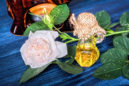 aceite de rosa esencial en el fondo de madera de color azul oscuro