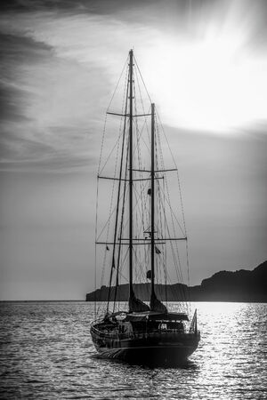 doomed: Old ship sailing to the sunset. Dramatic dark evening sea view. Black and white
