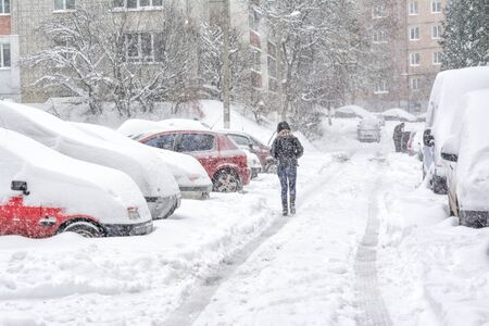 Snowstorm in Lviv, Ukraine in november 13, 2016. Snow-covered street and cars with a lonely pedestrian Stock Photo