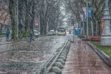 Lviv, Ukraine - December 12, 2016: Snowstorm with wet heavy snow and wind. Street view with cars and a lonely pedestrian