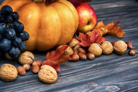 Kürbis, Apfel, Nüsse, Beeren mit Ahornblättern auf hölzernem Hintergrund. Herbst Karte Erntedankfest. Halloween